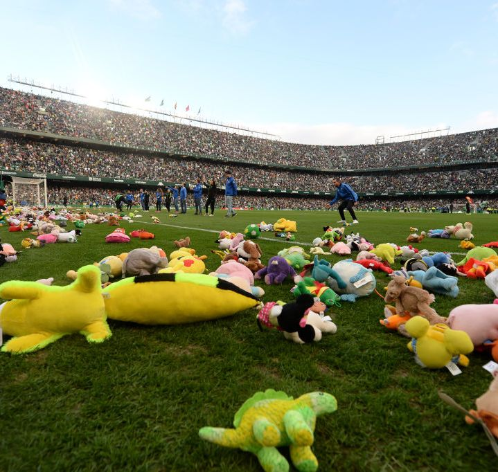 SEVILLE, SPAIN - DECEMBER 22: Fans throw toys onto the pitch for charity at half time of the Liga match between Real Betis Balompie and Club Atletico de Madrid at Estadio Benito Villamarin on December 22, 2019 in Seville, Spain. (Photo by Aitor Alcalde/Getty Images)