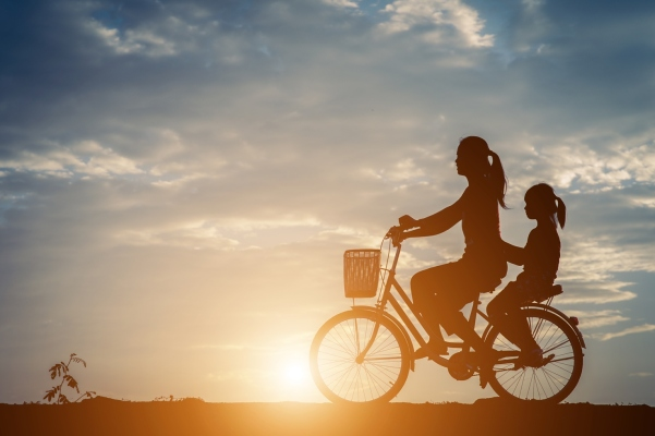Silhouette of mother with her daughter and bicycle