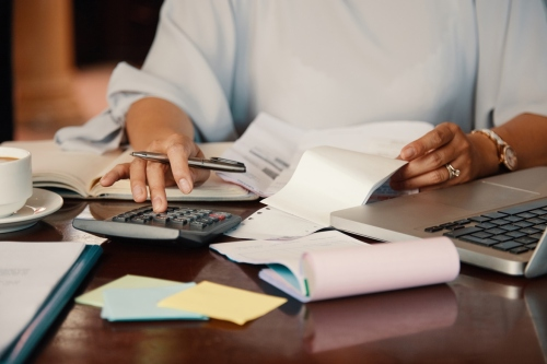 Hands of female entrepreneur working with bills and documents