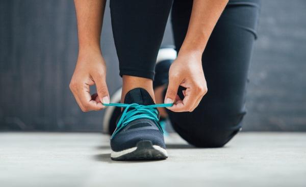 Female runner tying her shoes preparing for a run
